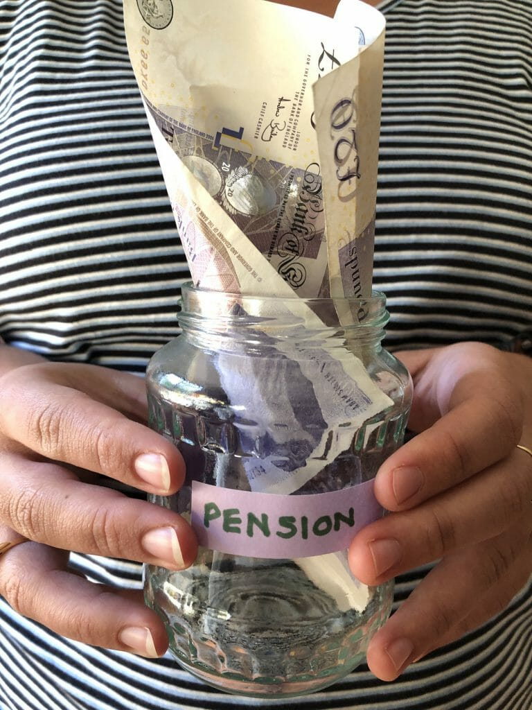 Millennial woman holding glass savings jar stuffed with British £20 banknotes and labelled Pension